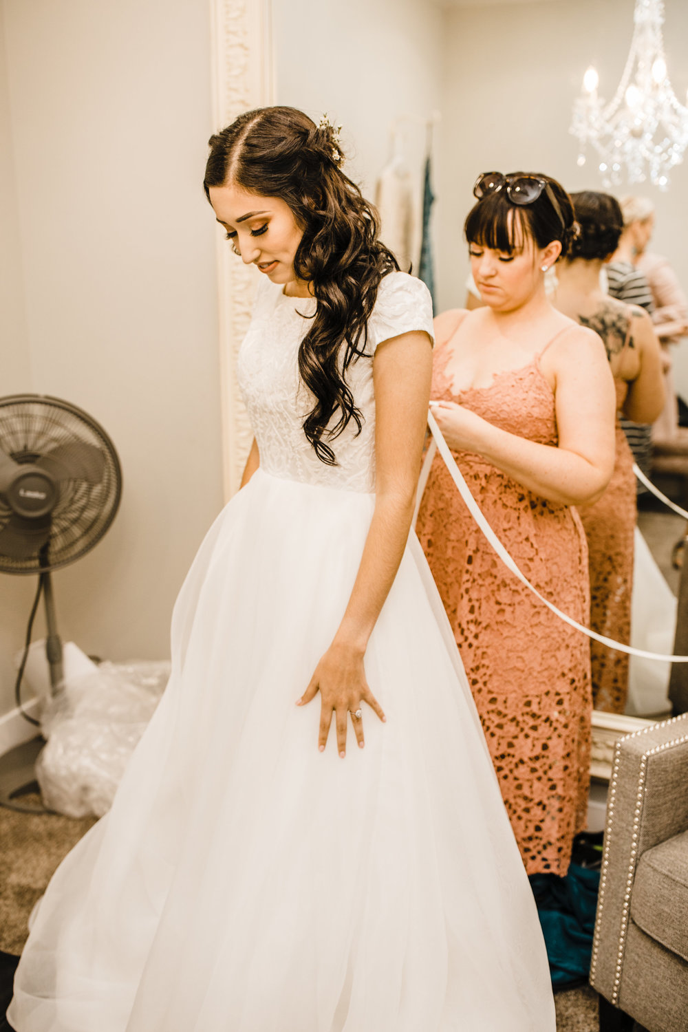 bride getting ready for the wedding day wedding dress tied up with ribbon bridesmaid helping bride into wedding dress orem utah wedding photography