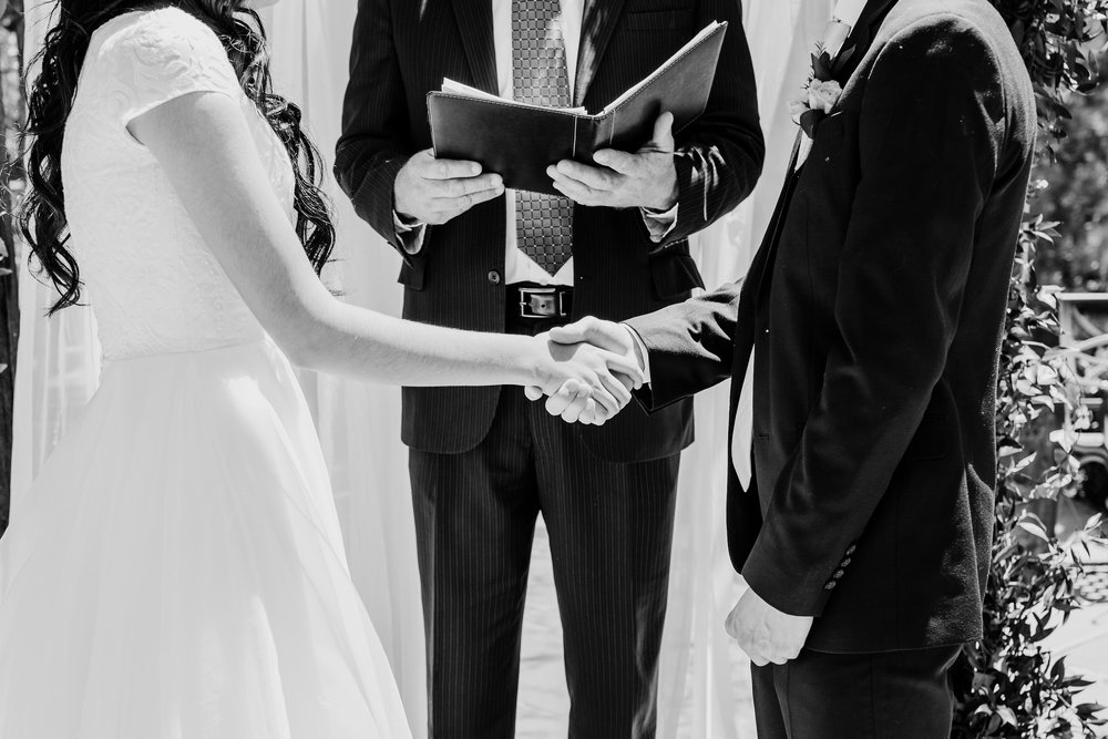 bride and groom hand in hand wedding ceremony black and white wedding photography