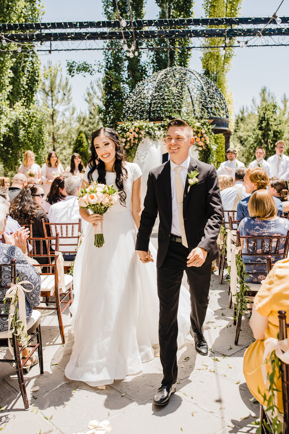 bride and groom after wedding ceremony walking down the aisle wedding lights orem utah wedding day photographer calli richards