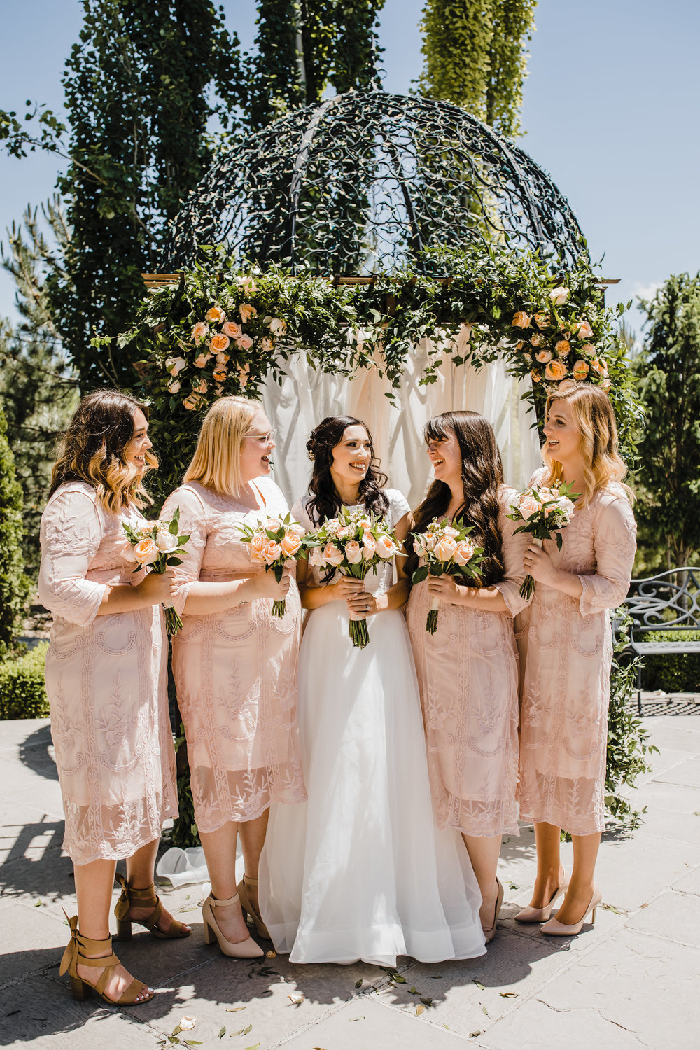 bridesmaids smiling with bride on wedding day blush lace bridesmaid dresses rose bouquets
