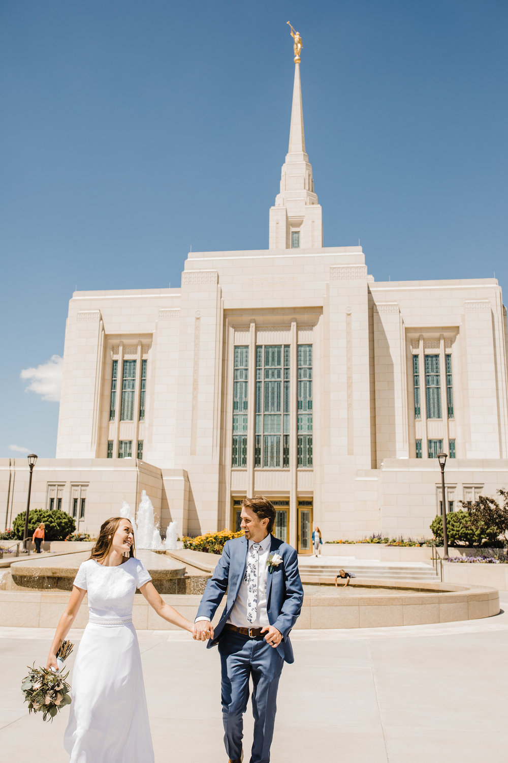 professional wedding photographer in logan utah temple exit lds holding hands laughing running