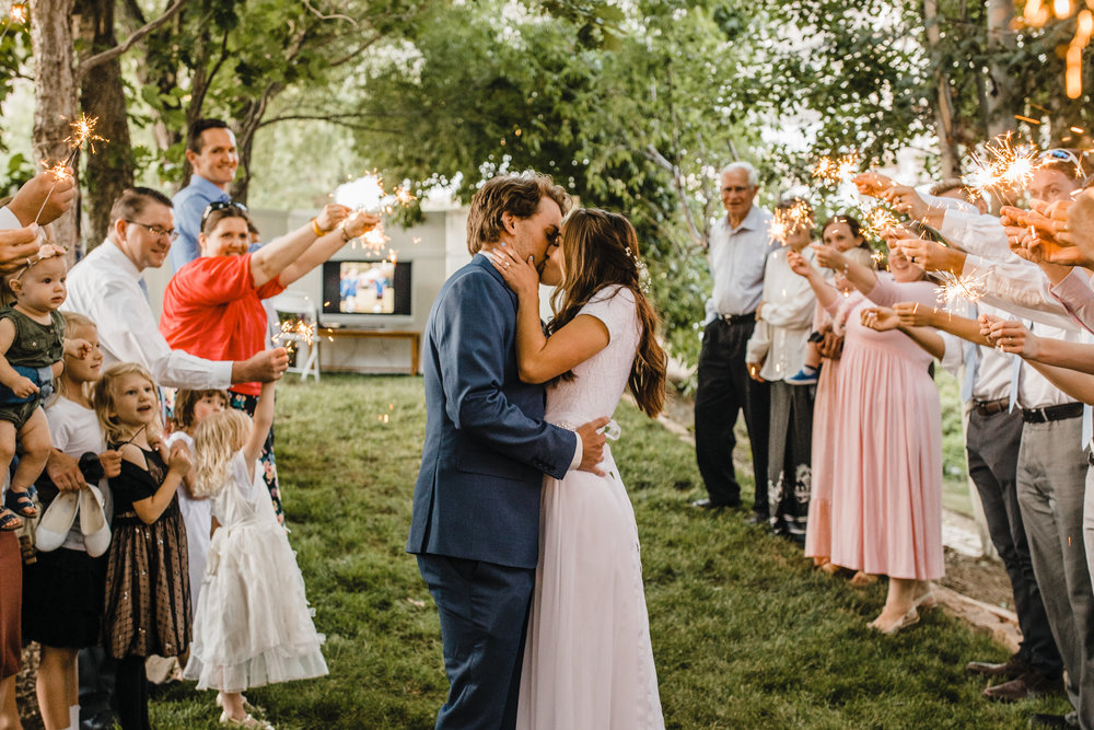 logan utah wedding photographer reception exit kissing romance sparklers boho wedding hair