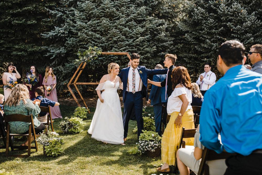 South Jordan wedding photographer outdoor wedding ceremony wedding exit holding hands happy