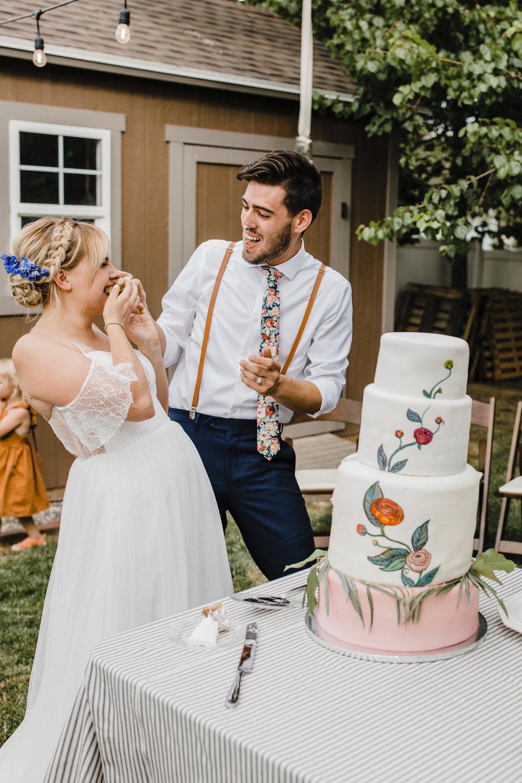 south jordan utah wedding photographer outdoor bohemian wedding string lights cutting cake stuffing faces smiling