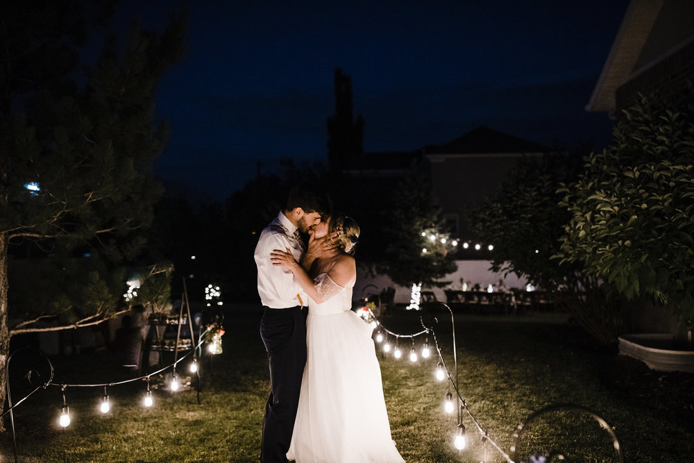 salt lake city professional photographer bohemian outdoor wedding reception wedding exit smiling happy romantic kissing string lights