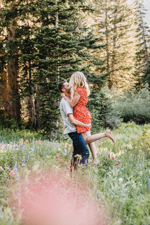 professional engagement photographer in alta utah hugging kissing romantic heel kick
