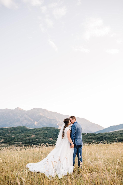 logan utah professional wedding photographer kissing mountains sunset fields