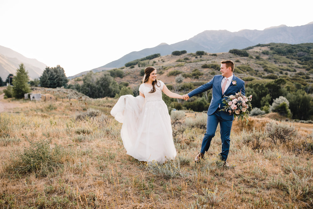 professional wedding photographer in logan utah bridals formals holding hands laughing filed mountains pink tie