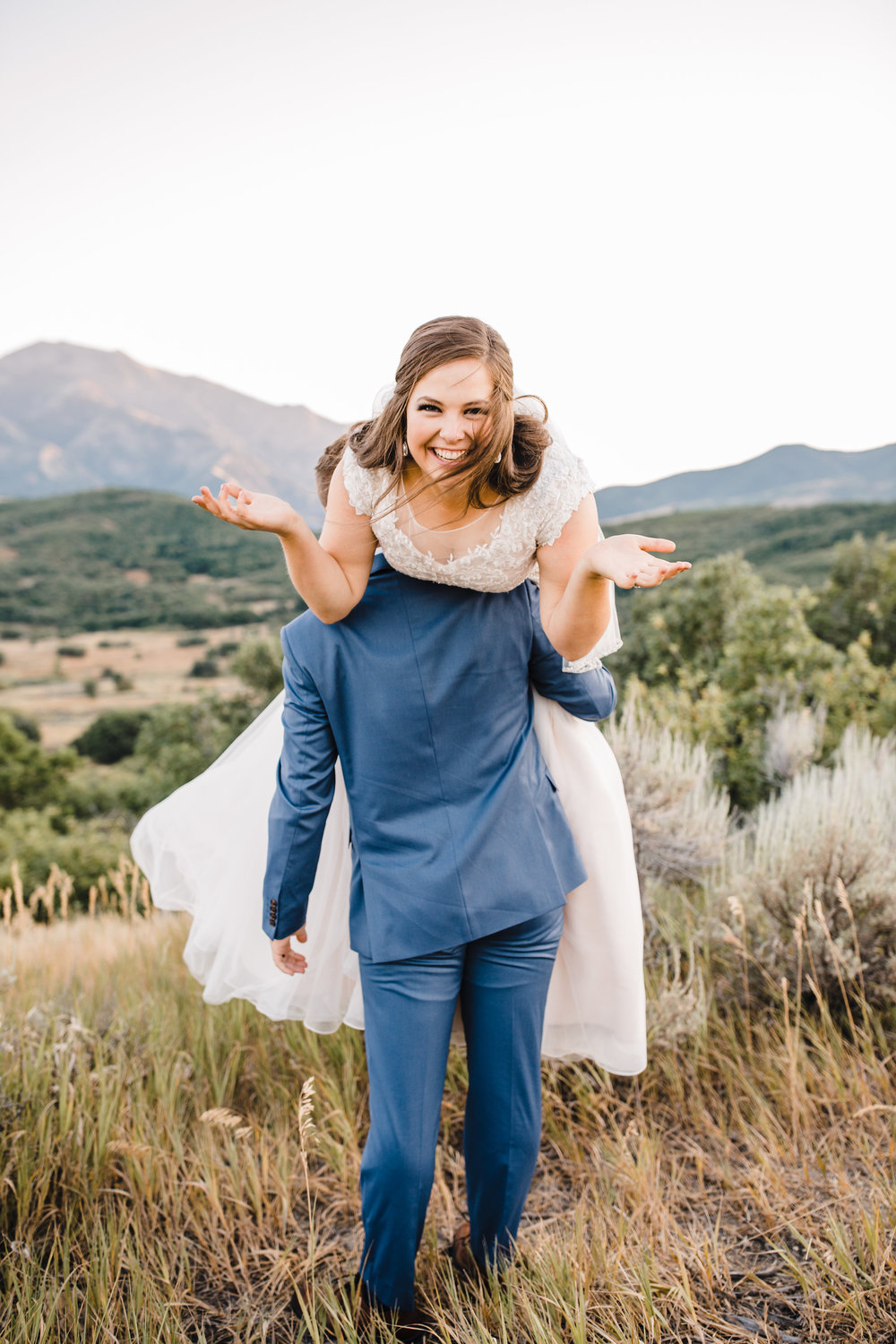 logan utah professional wedding photographer piggy back smiling laughing mountains silly