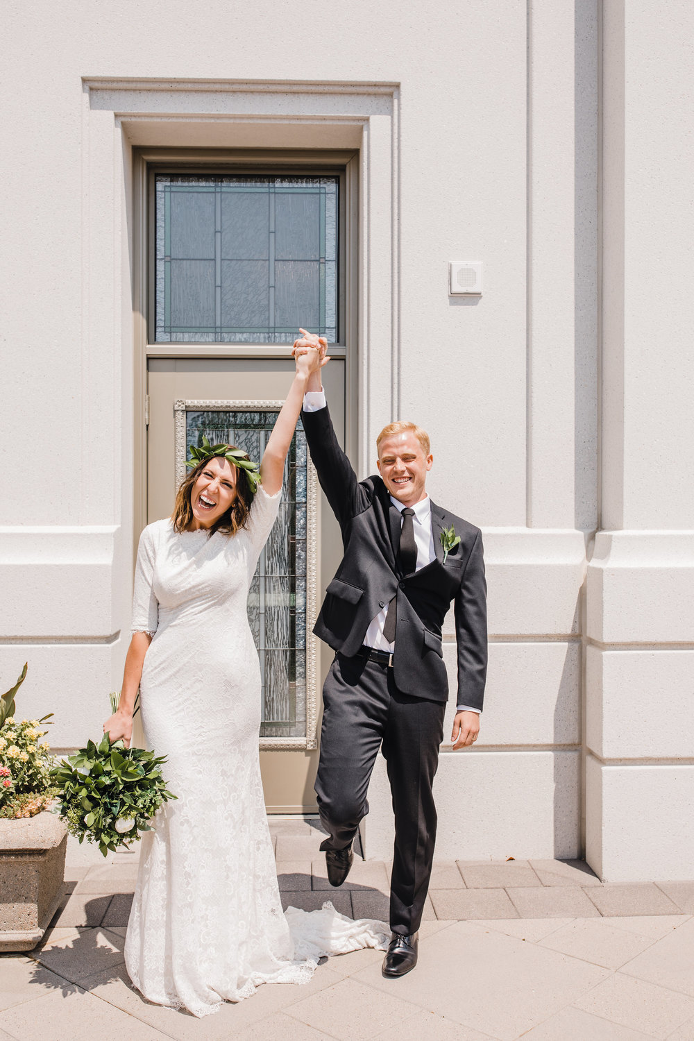 professional wedding photographer in brigham city utah temple exit lds holding hands cheering happy
