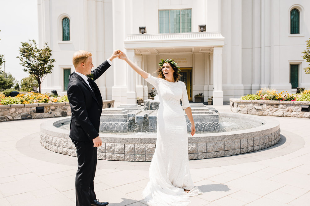 brigham city wedding photographer utah lds temple spinning dancing happy smiling holding hands fountain
