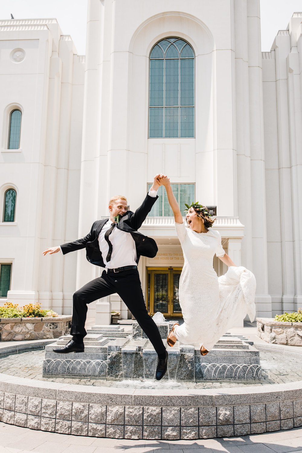 brigham city professional wedding photographer fountain jumping holding hands laughing smiling