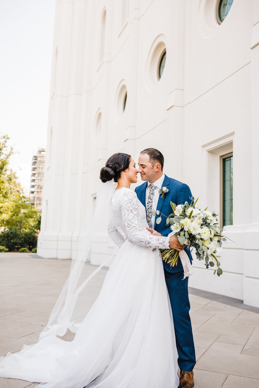 professional wedding photographer in brigham city utah smiling temple grounds long veil hugging