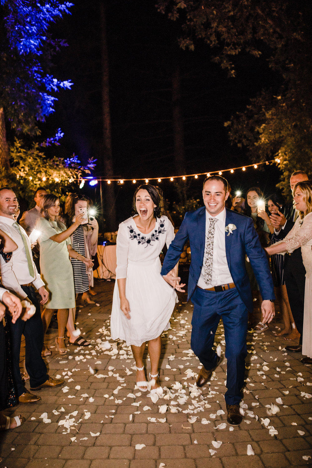 professional brigham city utah photographer wedding reception exit string lights flowers happy holding hands cheering
