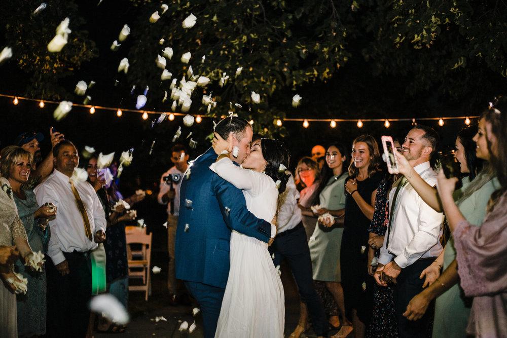 brigham city utah wedding photographer outdoor reception exit flowers string lights kissing cheering