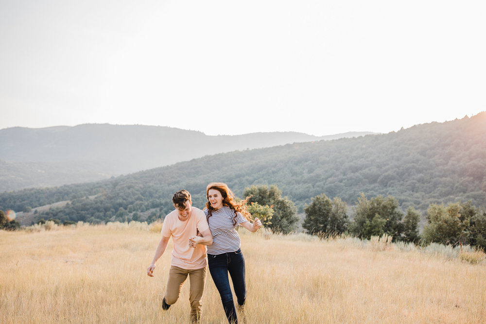 sardine canyon engagement photographer holding hands racing running laughing mountain backdrop