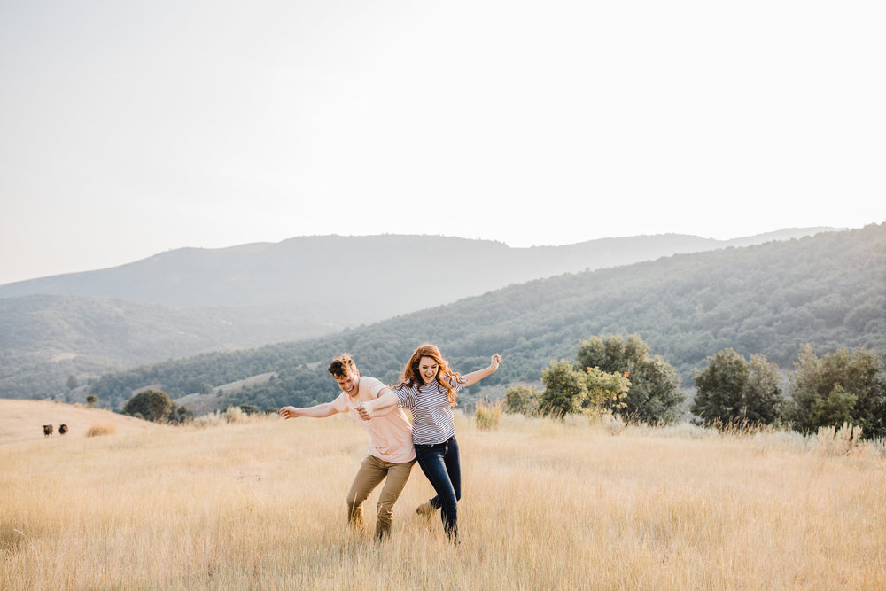 cache valley engagement photographer running bumping smiling laughing mountains fields happy