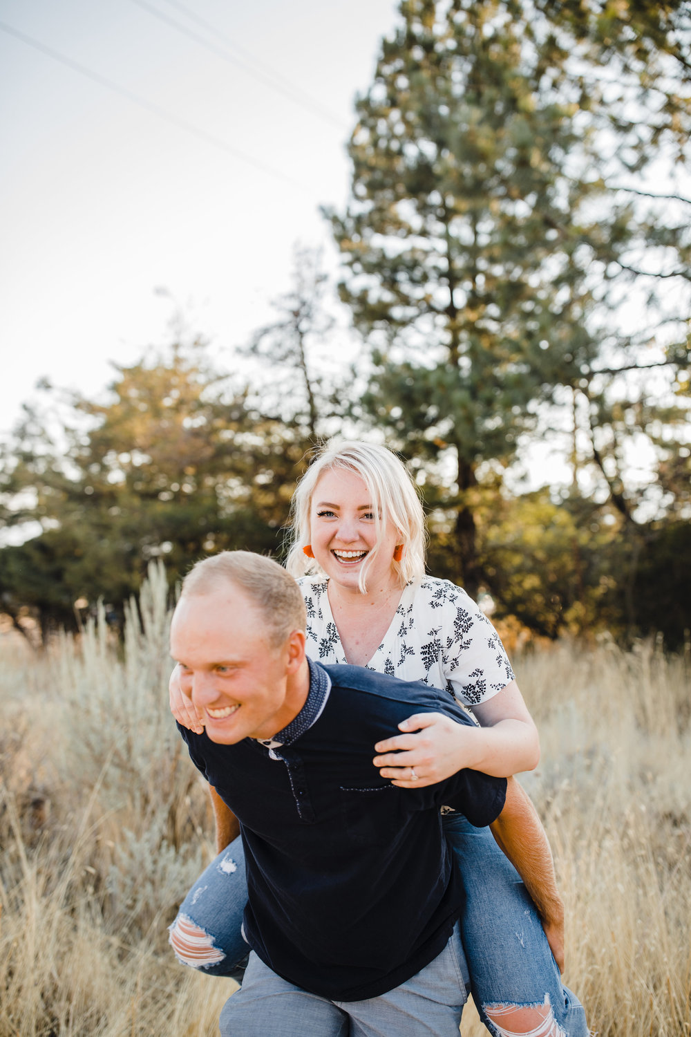 logan utah professional couples photographer piggy back field smiling happy laughing