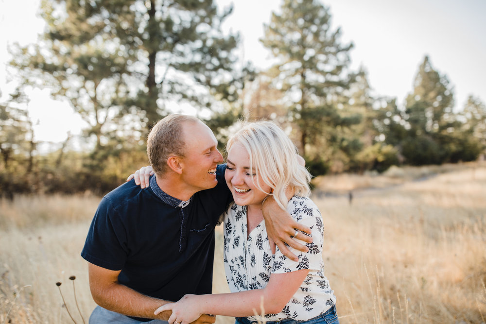 professional logan utah couples photographer field backdrop laughing hugging playful
