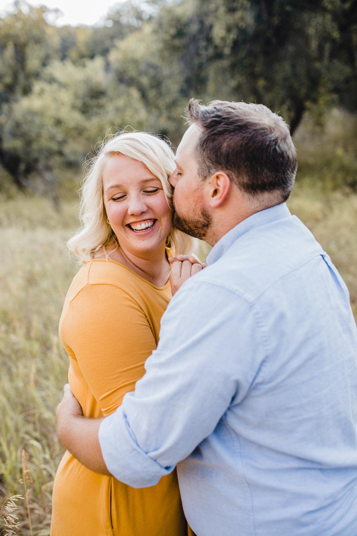 professional mantua utah engagement photographer marigold dress hugging laughing ear whispering