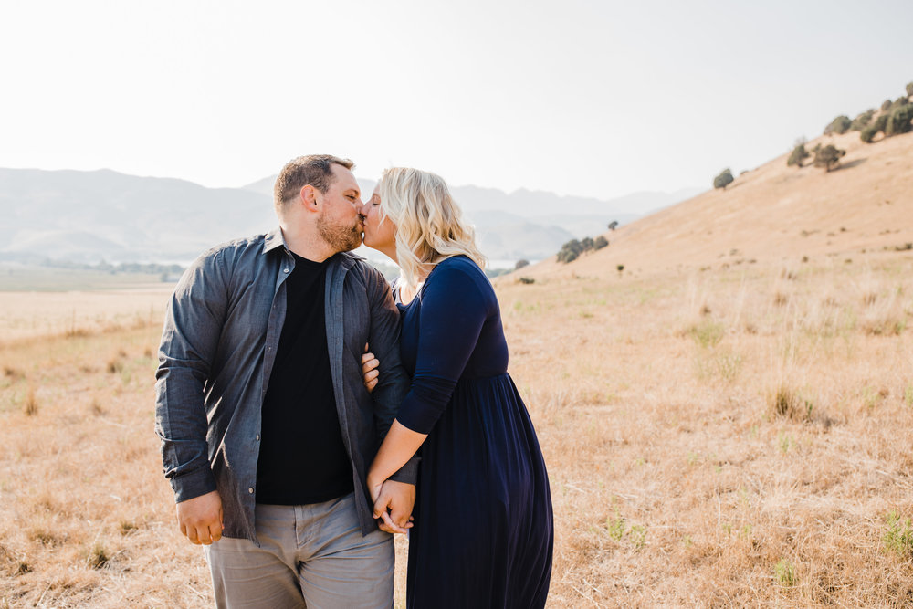 engagement photographer in brigham city utah mountains kissing romantic hugging linked arms