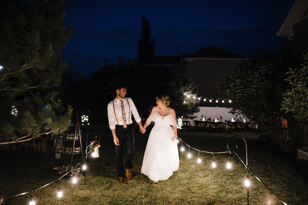 nightime secret bride and groom exit string lights reception boho wedding dress floral tie suspenders bride and groom walking holding hands wedding photographer salt lake city utah
