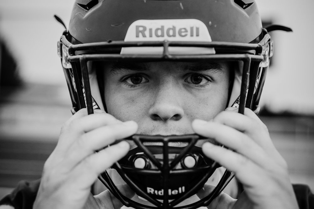 professional senior portrait photographer helmet football serious