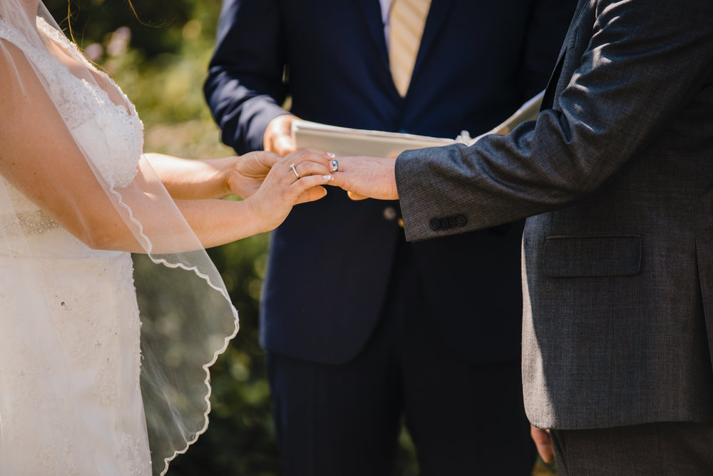 olympia washington professional wedding photographer wedding bands exchanging outdoor wedding arch