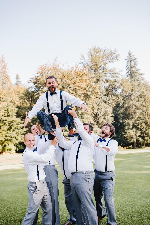 olympia washington professional wedding photographer groomsmen tossing jumping happy celebrating