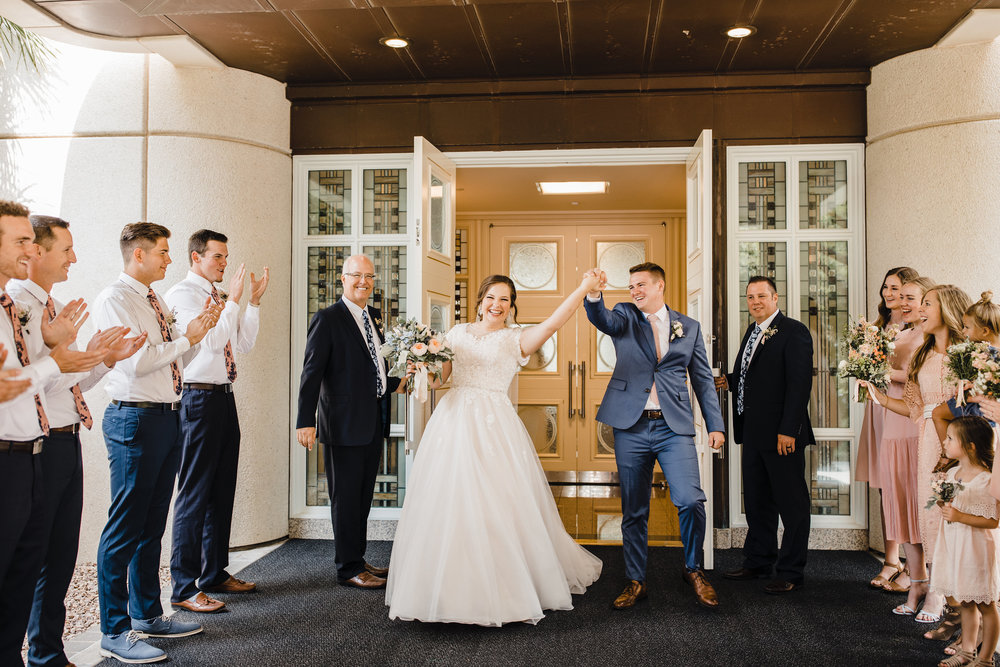 professional wedding photographer in las vegas wedding exit cheering lds temple holding hands