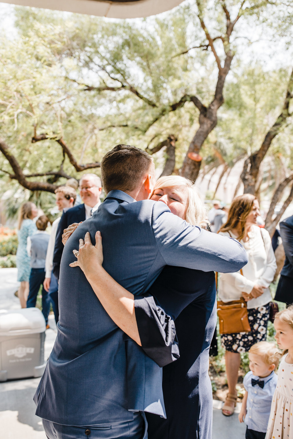 professional las vegas wedding photographer wedding exit celebrating hugging mother of the groom