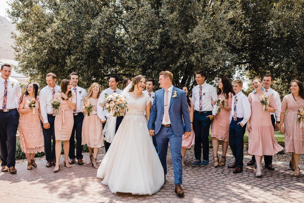 professional las vegas wedding photographer wedding party petal pink brides maids groomsmen walking cheering laughing