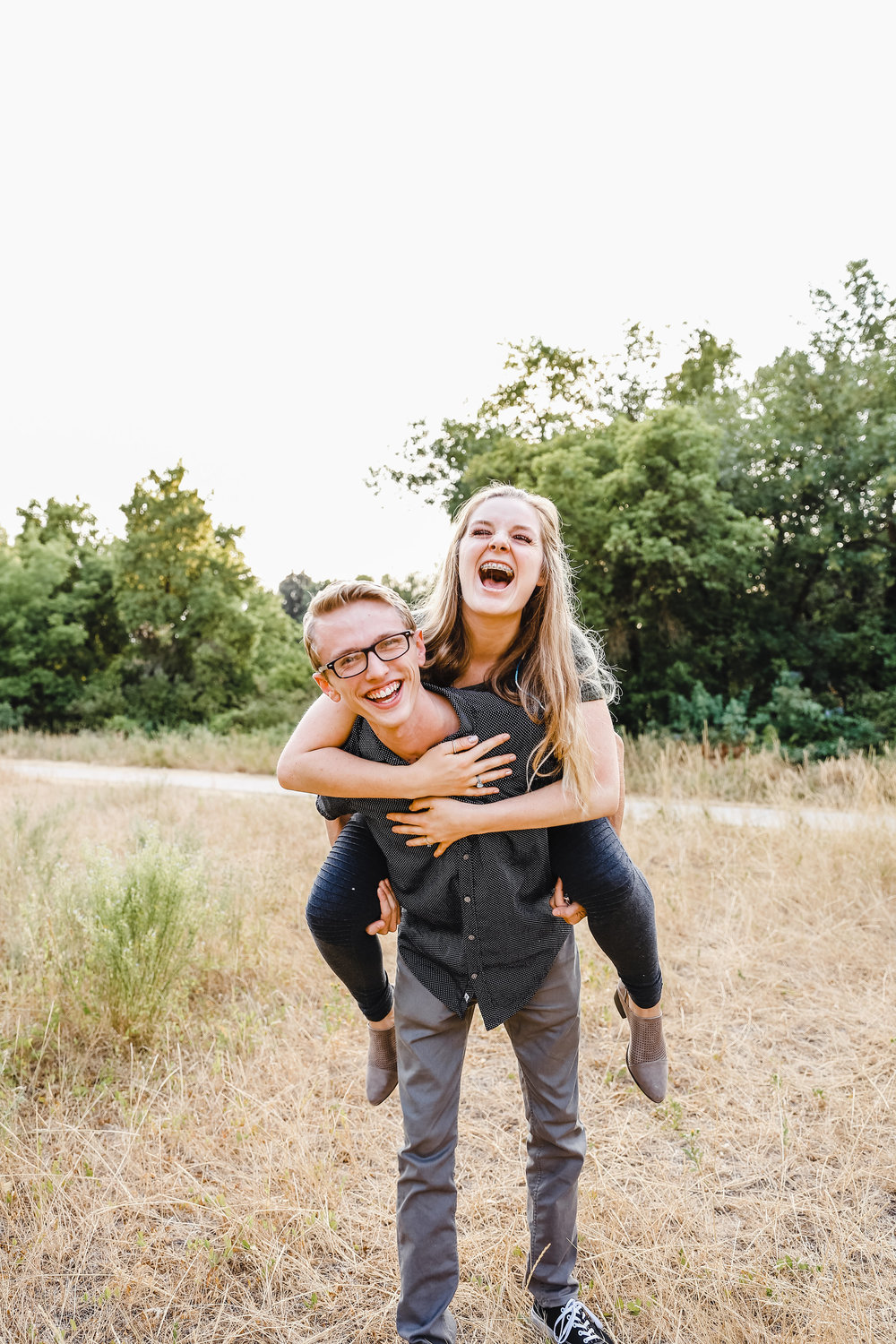 professional couples photographer in logan utah smiling laughing piggy back playful