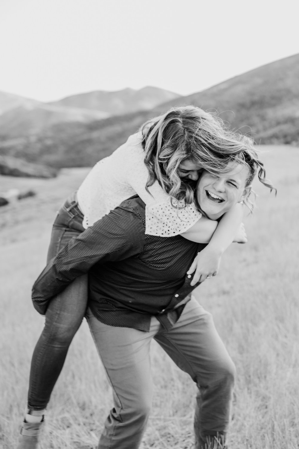 logan utah engagement photographer professional piggy back flying curls mountains black and white
