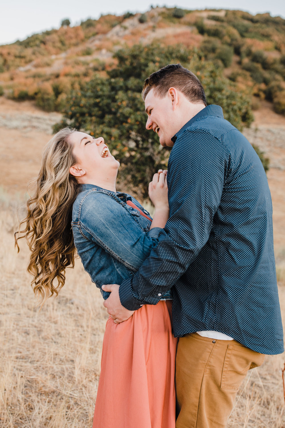 professional logan utah engagement photographer laughing hugging playful desert