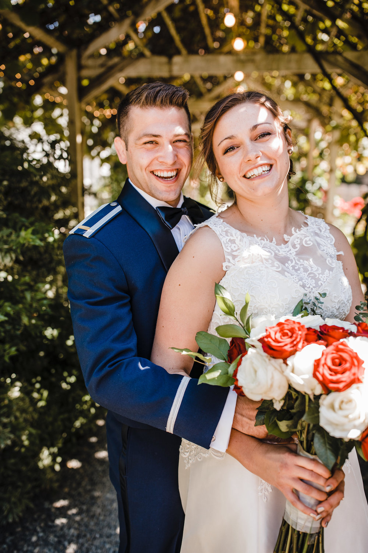 professional wedding photographer olympia washington military wedding hugging smiling laughing red roses