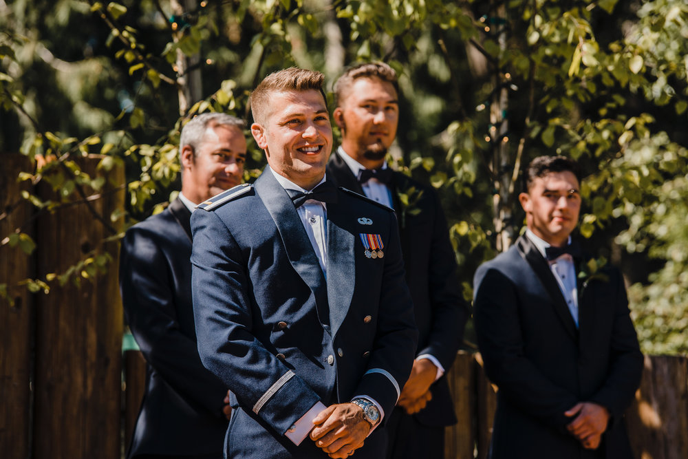 professional olympia washington wedding photographer groom outdoor ceremony wedding arch smiling