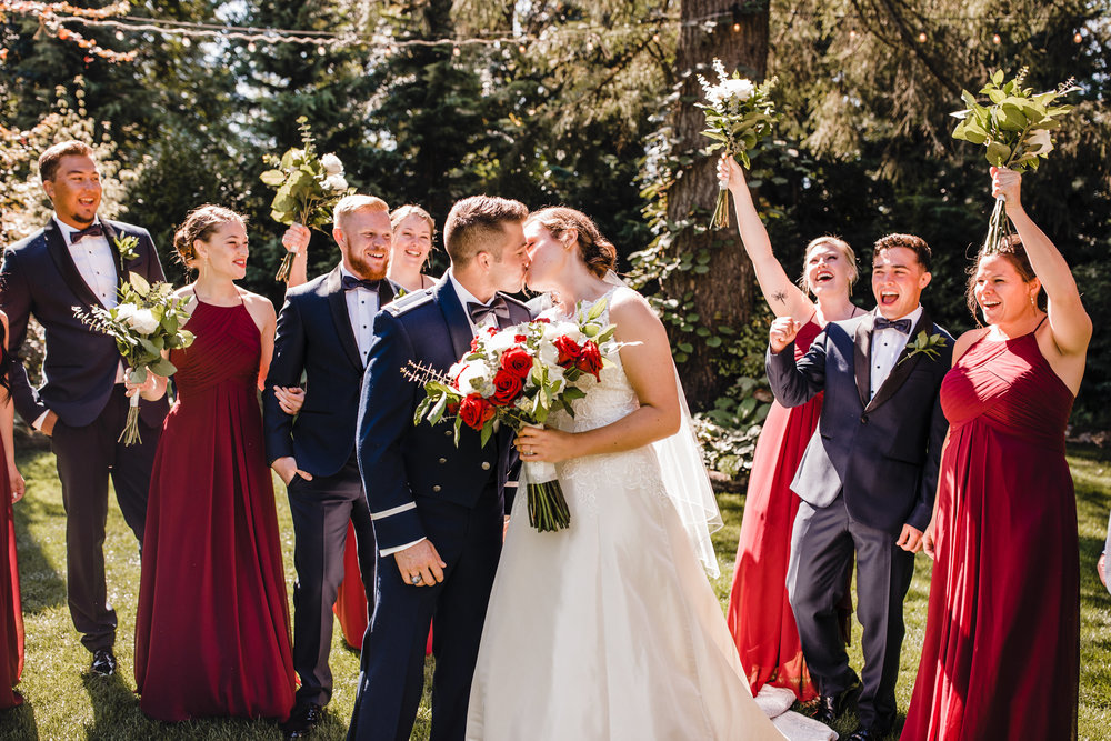 best olympia washington photographer cheering wedding party red bridesmaids dresses kissing happy outdoor ceremony