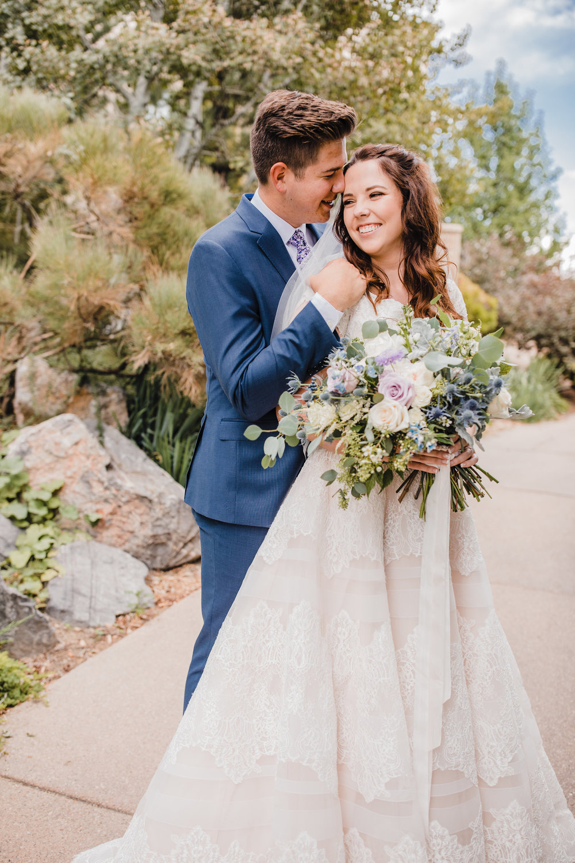 professional utah valley wedding photographer smiling hugging neutral bouquet