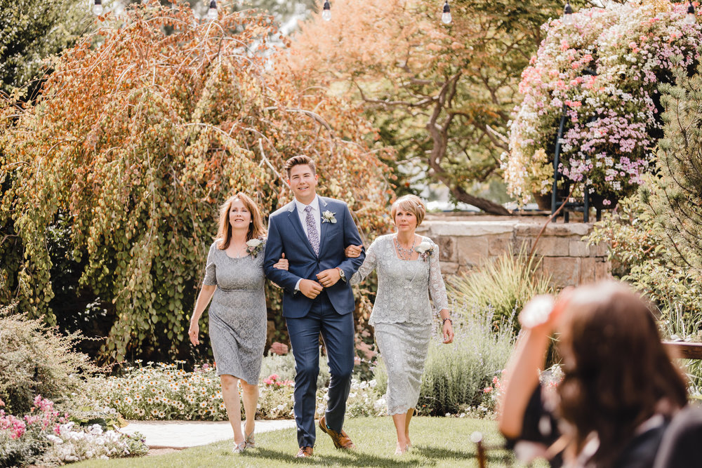 utah valley wedding photographer outdoor ceremony groom and mother step mom holding hands isle