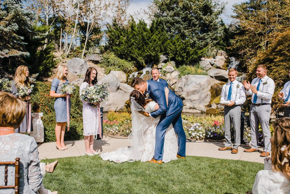 professional utah valley photographer outdoor wedding ceremony kissing dip romantic cheering