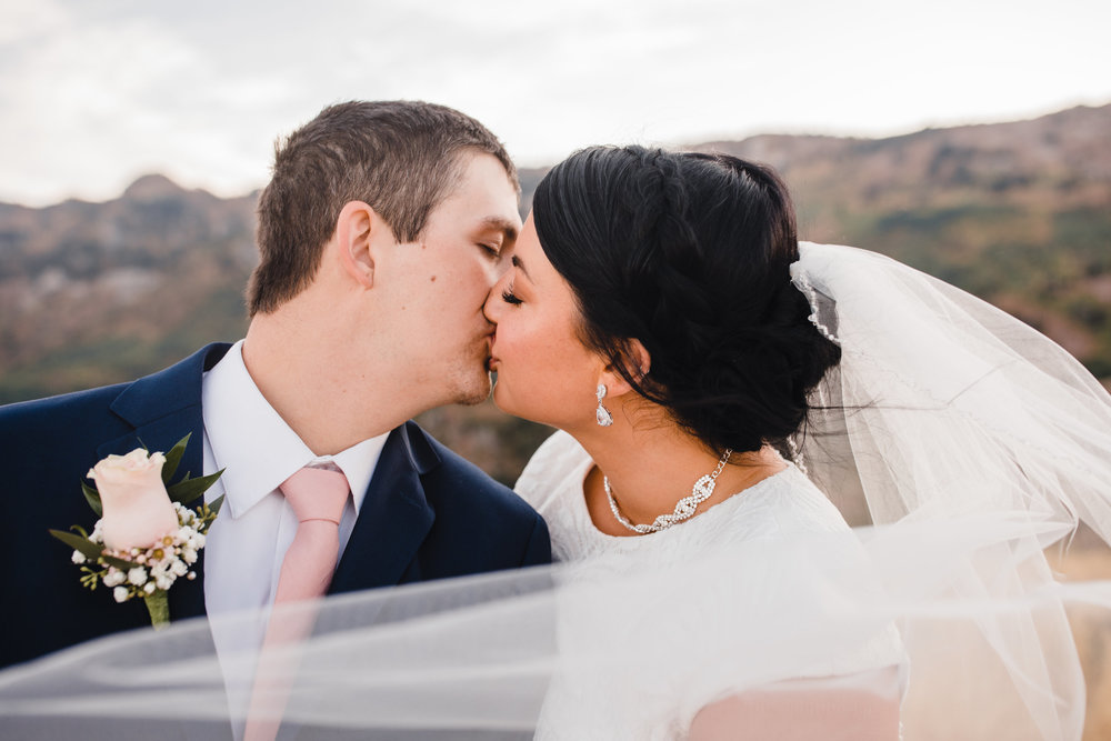 best formal photographer cache valley utah kissing windy veil romantic mountain backdrop