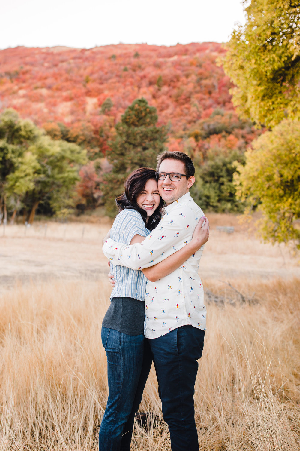 professional logan utah engagement photographer hugging happy red leaves