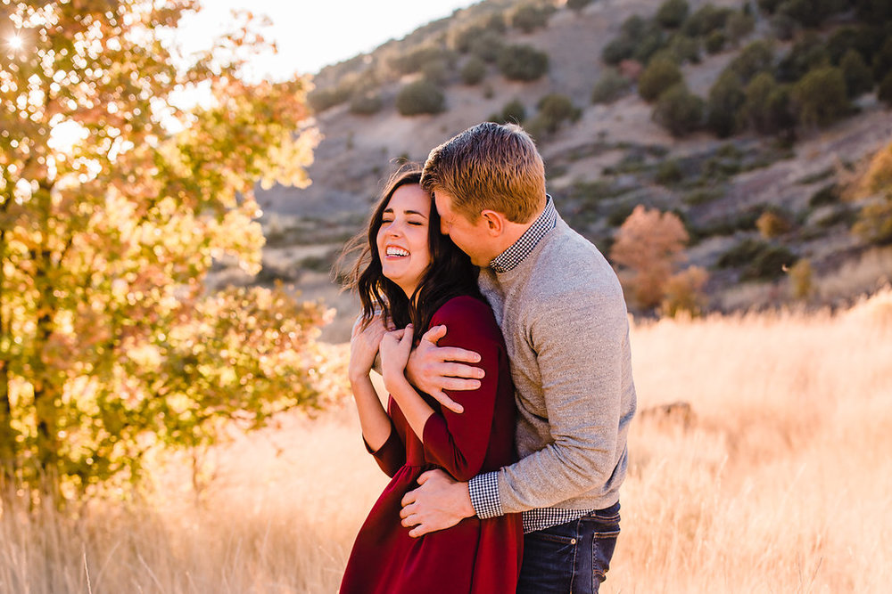 cuddling and kissing engagement photos autumn leaves red dress engagement outfits calli richards logan utah engagement photographer beautiful couple