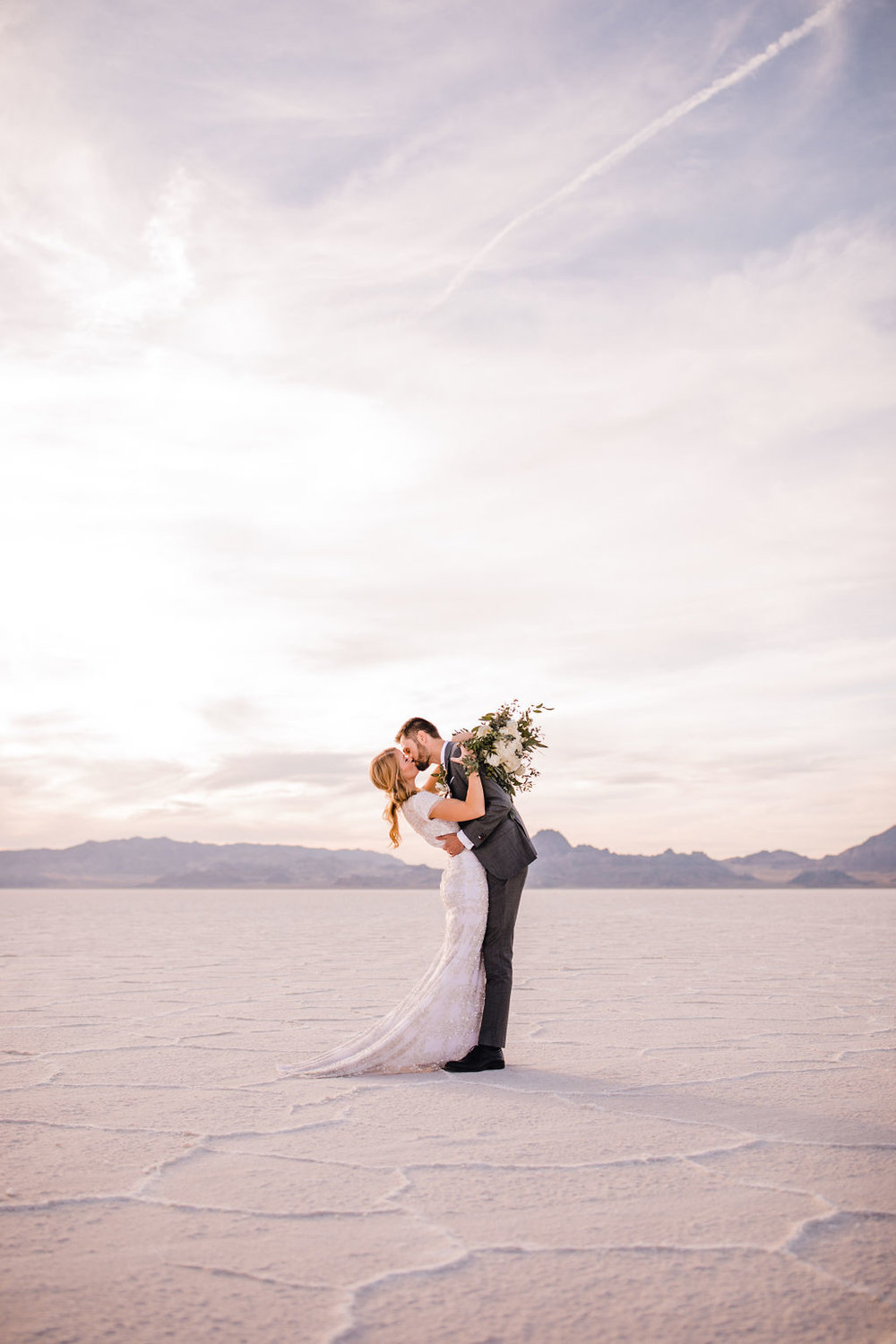 professional salt lake city formal photographer salt flats sunset whispy clouds kissing romantic hugging white bouquet