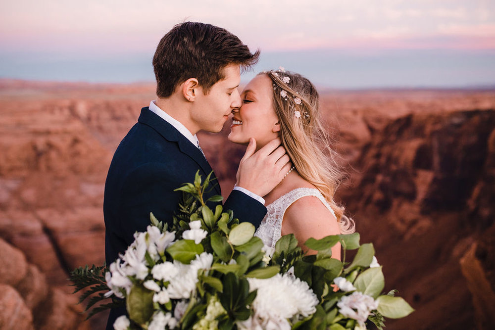 best grand canyon formal photographer kissing romantic sunset bohemian hair white floral bouquet