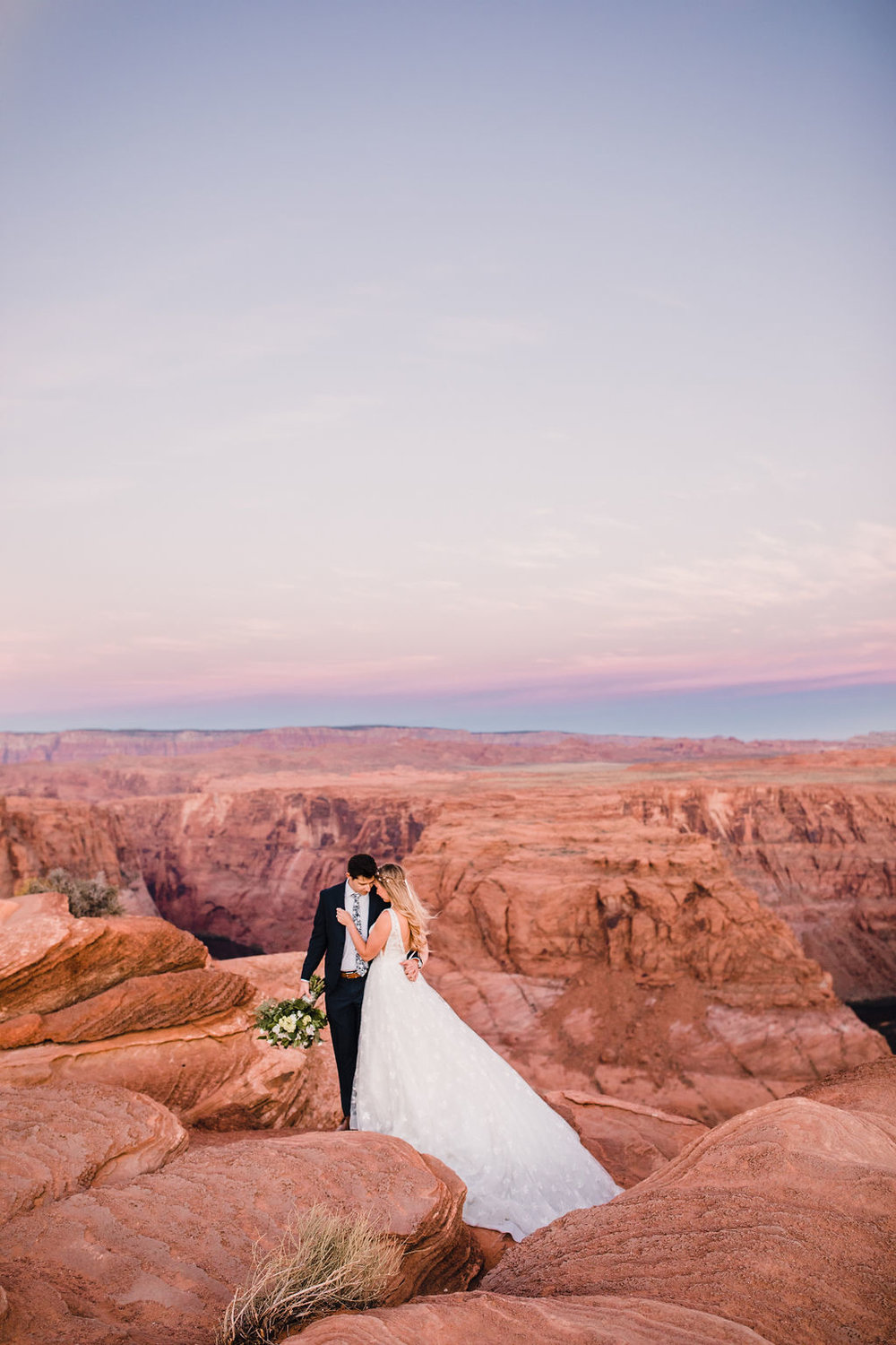 page arizona formal photographer hugging red rocks romantic sunset bohemian bride