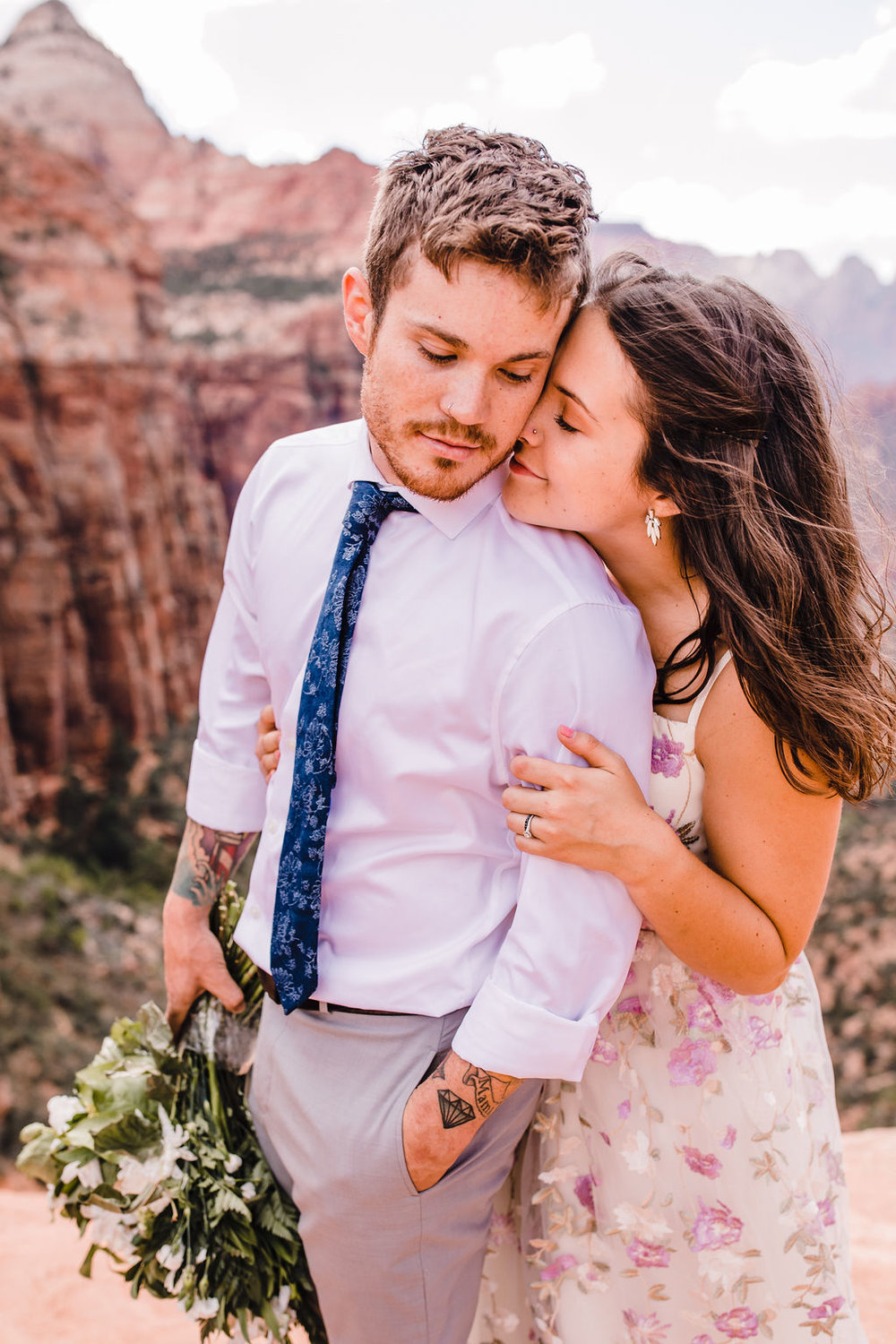 professional grand canyon formal photographer pink floral wedding dress red rocks kissing romantic