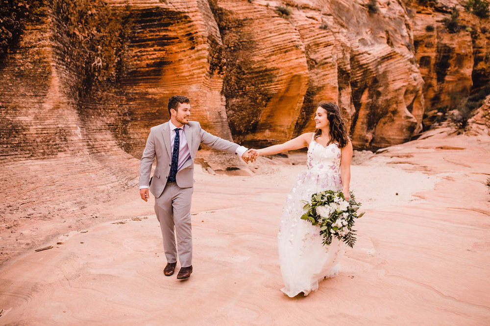 best page arizona formal photographer pinkn floral wedding dress white bouquet holding hands grand canyon