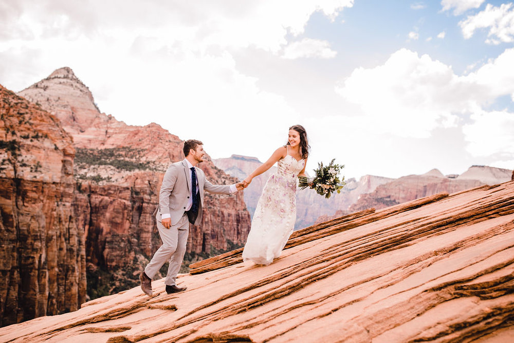 best horseshoe bend formal photographer pink floral wedding dress holding hands laughing red rocks grand canyon